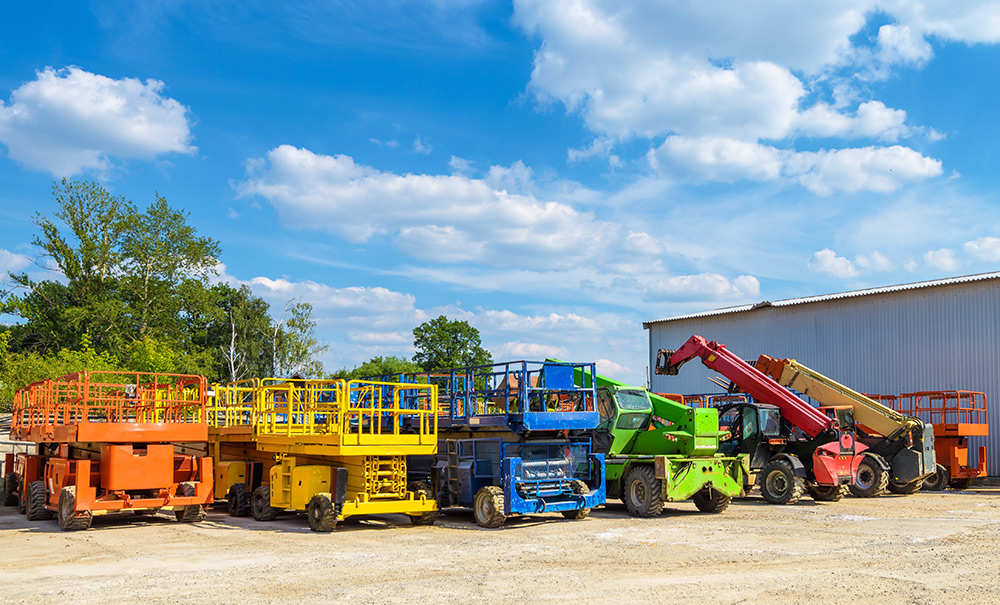 a row of scissor and boom lifts painted orange, yellow, blue, green, red, and white
